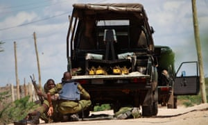 Kenyan soldiers take cover as shots are fired in front of Garissa university in Garissa town, near the border with Somalia.