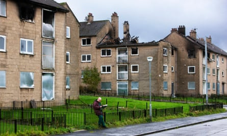 A man reads the newspaper in Easterhouse, Glasgow, once one of the most dangerous parts of Europe.