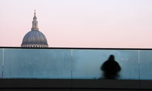 A homeless man sitting on Millenium bridge, with St. Paul's cathedral dome in the background.