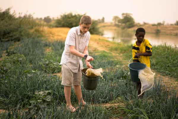 George helps Ayabil with the job of watering the family plot with buckets of water drawn from the river.