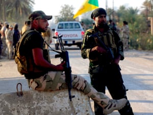Shia fighters guard a checkpoint just south of Baghdad.