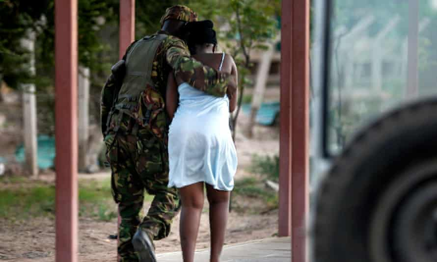 A Kenyan soldier escorts a woman out of the building after she was rescued.