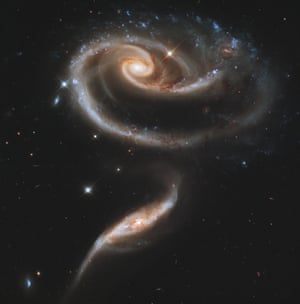 A pair of interacting galaxies called Arp 273. The larger of the spiral galaxies, known as UGC 1810, has a disk that is distorted into a rose-like shape by the gravitational tidal pull of the companion galaxy below it, known as UGC 1813.