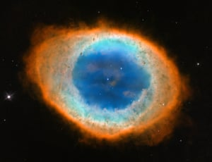 The Hubble's image of the Ring Nebula, the glowing shroud around a dying Sun-like star. The pictures Hubble was able to capture allowed astronomers to construct a precise three-dimensional model of the glowing gas shroud, called a planetary nebula.