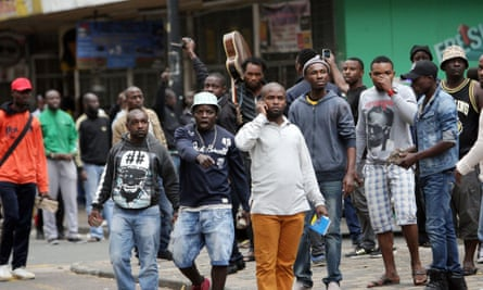 Foreign nationals stand with stones and bricks after a skirmish with locals in Durban.