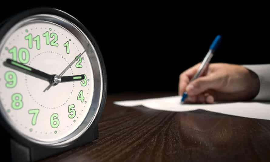 clock with a man doing written test in the background,useful for job application.education and other testing related