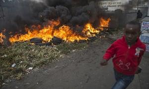 TOPSHOTS A child runs pass burning tires