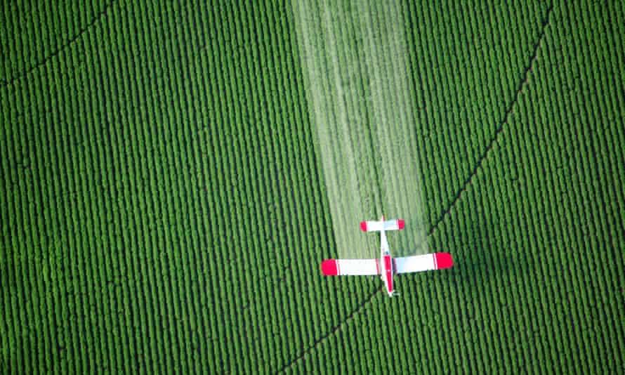 A crop duster sprays farmland