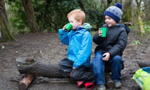 Students have a hot chocolate break in the forest.