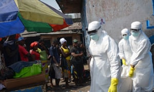 Red cross workers, wearing protective suits, carry the body of a person who died from Ebola during a burial with relatives of the victims of the virus, in Monrovia, on January 5, 2015.