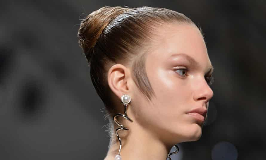Hair styled flat to the side of a model's face on the  Balenciaga runway.