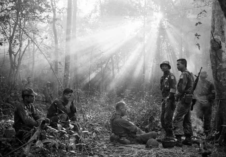 South Vietnamese troops and their US advisers resting in the jungle near the town of Binh Gia, 40 miles east of Saigon, in January 1965.
