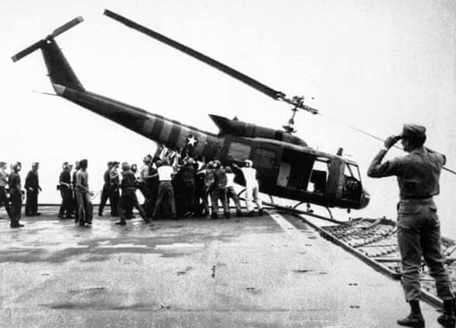 29 April 1975: US navy personnel aboard the USS Blue Ridge push a helicopter into the sea off the coast of Vietnam in order to make room for more evacuation flights from Saigon.