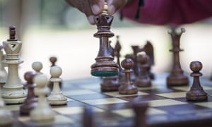 Hand moving chess piece on board, close upkennychess
