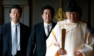 Japan's Prime Minister Shinzo Abe (C) is led by a Shinto priest as he visits Yasukuni shrine in Tokyo in this December 26, 2013 file photo. A Japanese cabinet member visited a shrine seen by critics as a symbol of Tokyo's wartime aggression on Wednesday, pouring salt on a fresh wound after Prime Minister Shinzo Abe's pilgrimage there last week drew sharp criticism from China and South Korea. REUTERS/Toru Hanai (JAPAN - Tags: POLITICS CONFLICT):rel:d:bm:GF2E9CQ08UC01