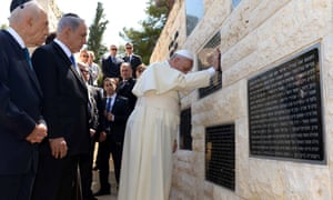 Pope Frances puts his hands on a plaque at Mount Herzl cemetery in Jerusalem honouring victims of terrorism