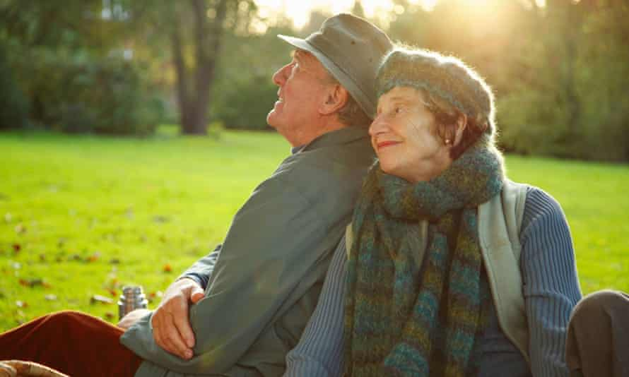 Older couple sitting on the grass in a park