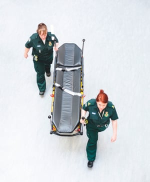Two NHS workers push an empty trolley