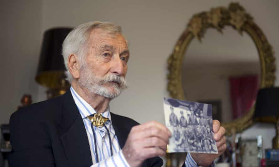At home in Houilles, holding up a photo of the members of his unit during the second world war.
