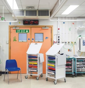 Trollies and an empty chair in a hospital room