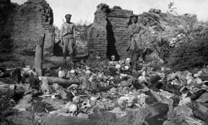 Soldiers standing over skulls of victims from the Armenian village of Sheyxalan, during the first world war.
