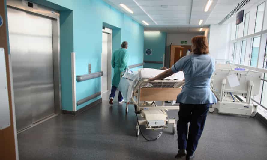 A nurse wheels a patient along a hospital corridor