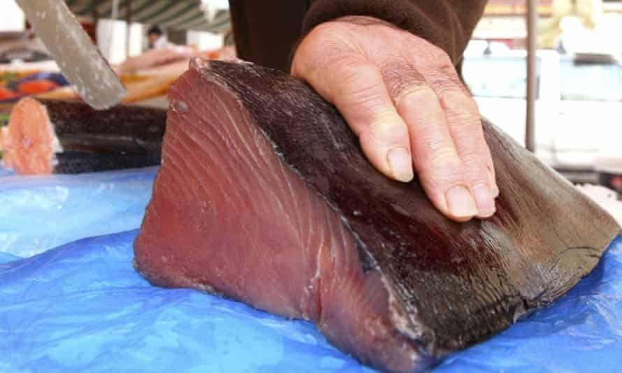 A fishmonger cuts a joint of Bluefin tuna, which was caught off of Thailand. The European Union is to give Thailand six months to drastically change its policies on illegal and unregulated fishing or face an EU fish import ban.