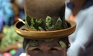 An Aymara woman with dried coca leaves decorating the brim of her hat