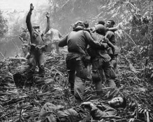 As fellow troopers aid wounded comrades, a paratrooper of A Company, 101st Airborne Division, guides a medevac helicopter through the jungle foliage to pick up casualties suffered during a five-day patrol near Hue, April 1968