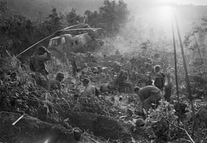 Marines emerge from their foxholes south of the DMZ after a third night of fighting against North Vietnamese troops, September 1966. The helicopter at left was shot down when it came in to resupply the unit