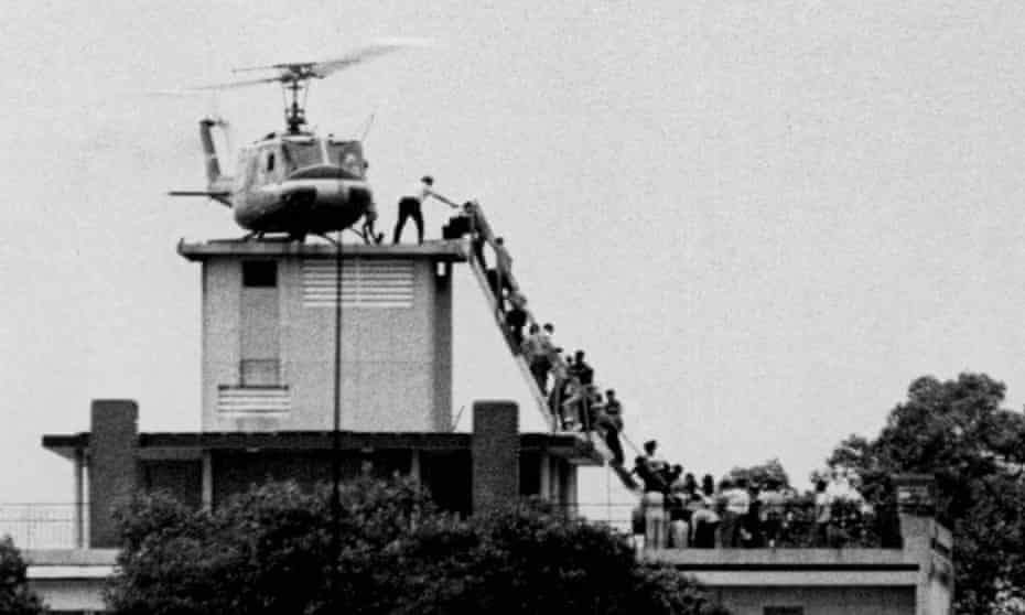 Evacuees are helped aboard an Air America helicopter perched on top of a building in Saigon.