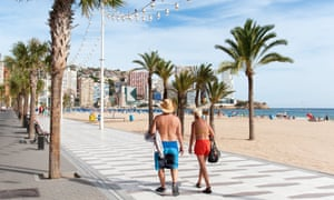 Tourists strolling along the promenade in Benidorm.