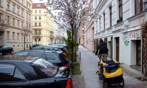 A man cycles along a residential street in Berlin, Germany.