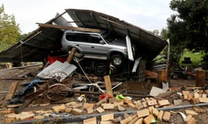 A tin shed roof comes down on the car of the Arkinstall family after severe storm conditions in Stroud, in the Hunter region of New South Wales.