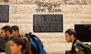 Israeli soldiers on Tuesday walk past the memorial stone in Hebrew bearing the name of Mohammed Abu Khdeir