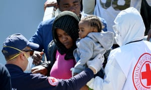 Rescued migrants are helped from an Italian navy ship after arriving in Augusta, Sicily.