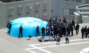 Investigators check a drone, under tarpaulin, on the roof of the prime minister's office. The camera-equipped drone produced a low level of radiation, police said.