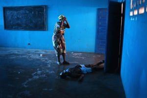 Omu Fahnbulleh stands over her husband Ibrahim after he fell and died in a classroom used for Ebola patients Winner, current affairs