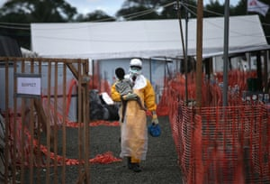 A Doctors Without Borders (MSF), health worker in protective clothing carries a child suspected of having Ebola at the MSF treatment centrein Paynesville, Liberia. The girl and her mother, both showing symptoms of the virus, survived and were released about a week later Winner, L'Iris d'Or