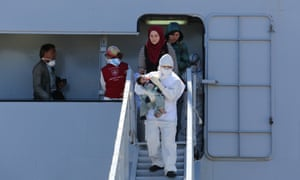 An officer feeds a baby as rescued migrants disembark from an Italian navy vessel in Augusta, Sicily.