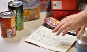 A volunteer selects food for a visitor's order at a foodbank charity in west London