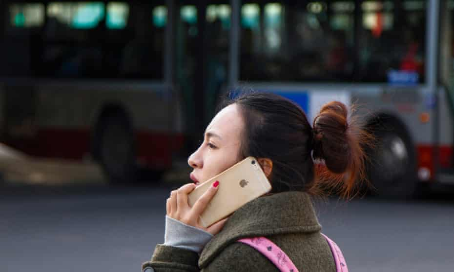 A woman uses her iPhone while waiting to cross an intersection in Beijing, China, 28 January 2015.