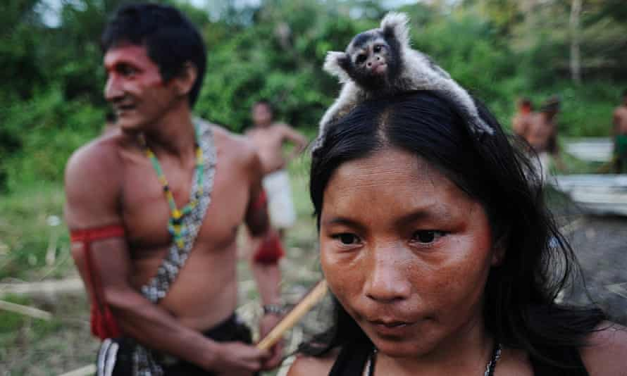 A Munduruku Indian woman warrior carries a monkey on her head in western Para state