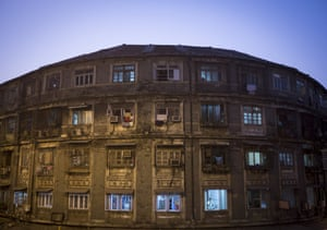 A man stands next to a window of a residential building in central Mumbai. Property prices range from 12,000 Indian rupees ($ 200) per square feet to 112,552 Indian rupees ($ 1800) per square feet