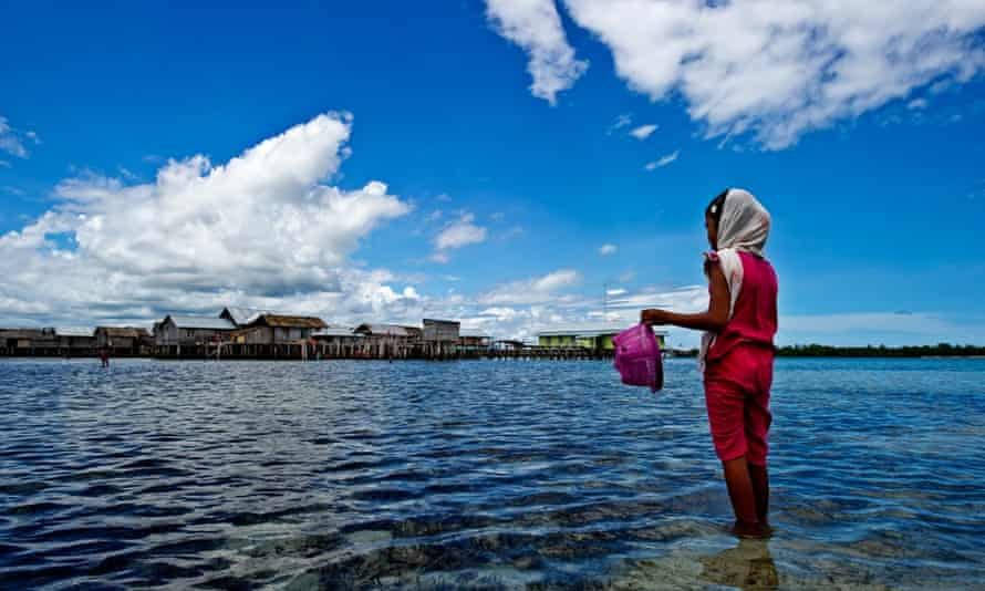 A little girl of the Sama Bajau ethnic group collects shellfish near her stilt village off the coast of Sulawesi, Indonesia