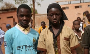 Fanta Bamba, 14, right, says her favourite subject is English. Bourama Fomba, 13, is a Man City fan and keen football player. Both are members of the school sanitation club.