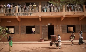 "A student washes his hands, outside section ""F"" in Sabalibougou, Bamako."