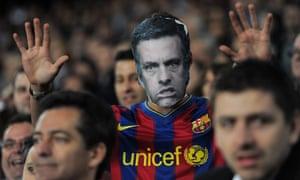 A Barcelona fan with a cardboard mask of José Mourinho.