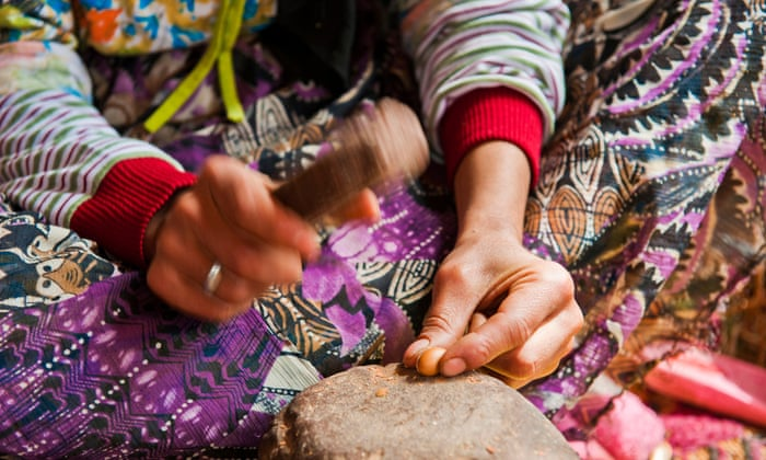 Berber woman cracking argan fruits