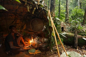 Baka man taking shelter in a Mongolu at a forest hunting camp, Cameroon